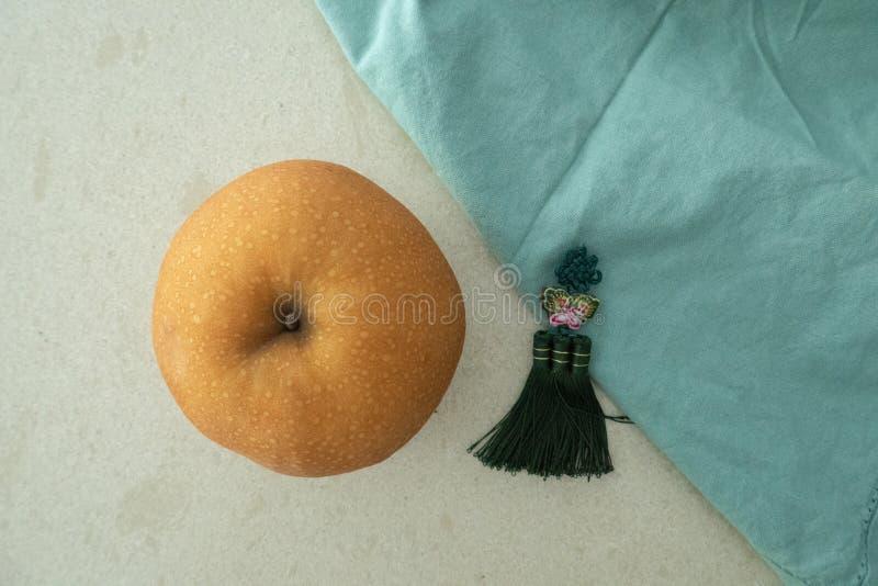 在一张大理石桌上的韩国梨与丝绸装饰品和蓝色织品 免版税库存图片