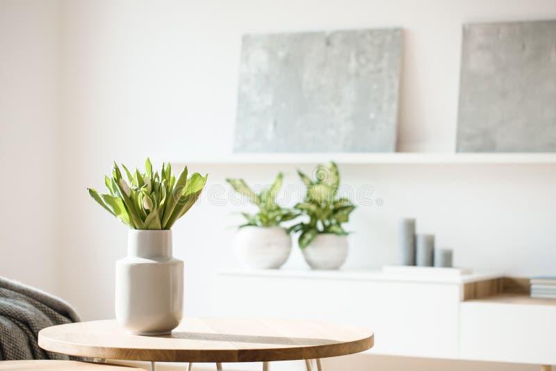 在一张小桌安置的白色花瓶的鲜花在明亮的ro 免版税图库摄影