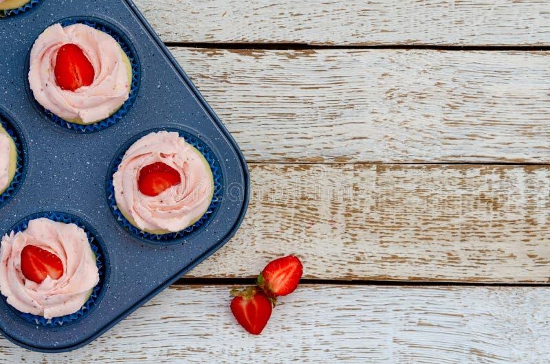 在一张平底锅白色木桌上的装饰的杯形蛋糕用草莓 免版税库存图片