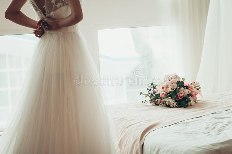 在一张床上的婚礼花束,当被弄脏的新娘按她的dre 库存照片