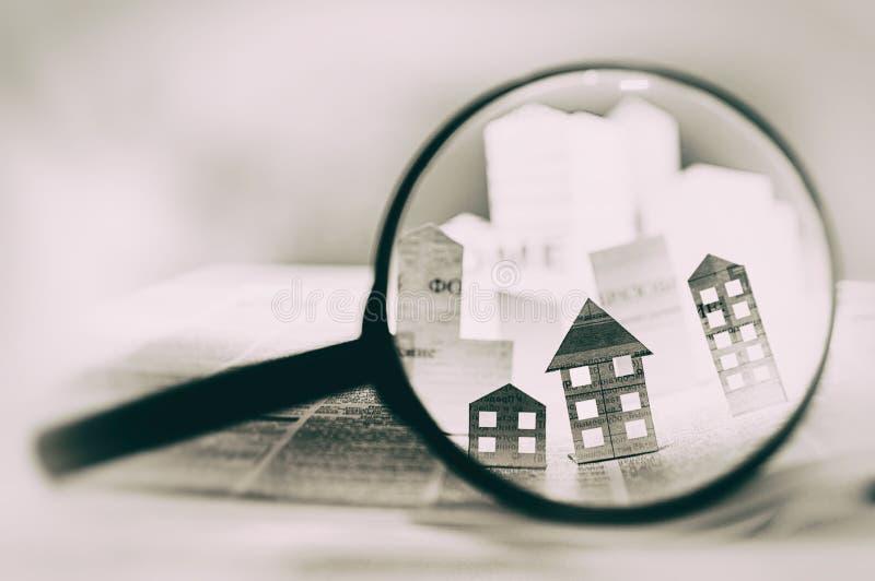 在一张开放报纸前面的放大镜与纸房子 免版税库存图片