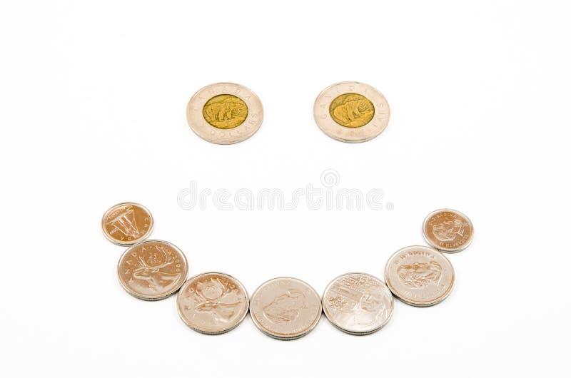在一张愉快的微笑的面孔安排的硬币 免版税库存照片
