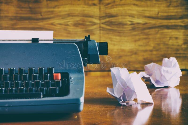在一张木书桌上的老减速火箭的蓝色打字机有被弄皱的纸的 免版税库存照片