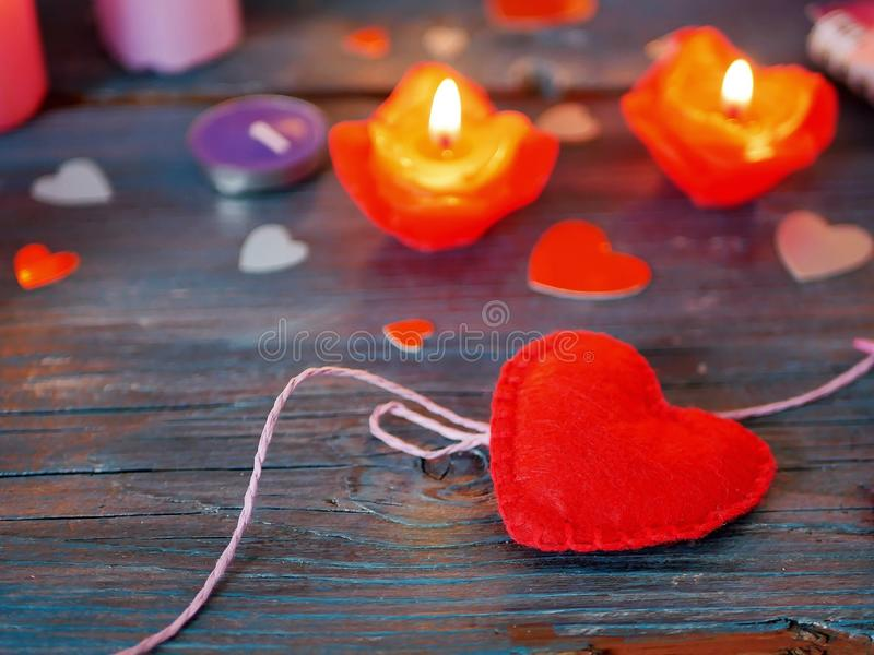 在一张木文本桌上的情人节装饰,毛毡一大红心和小纸心脏 免版税库存照片