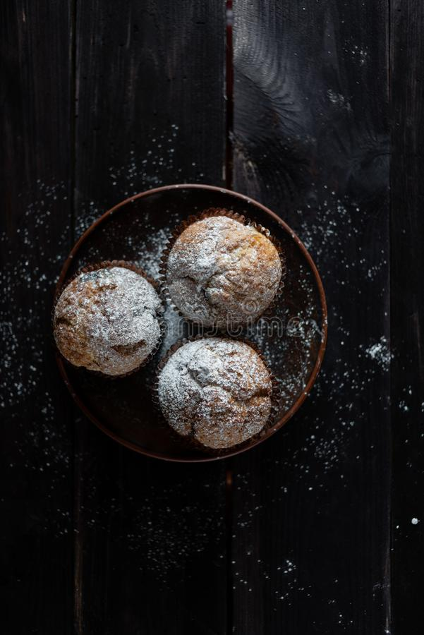 在一张木桌上的三个松饼洒与糖粉 免版税库存图片