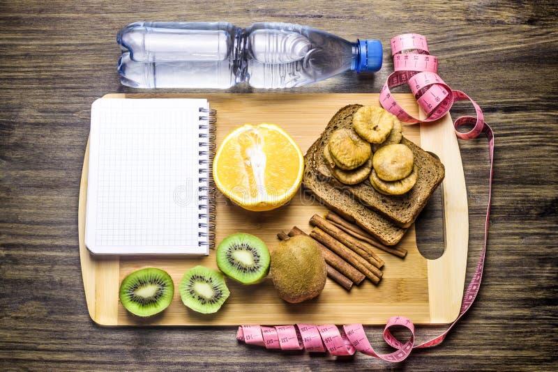在一张木桌上的健康食物 瓶水 写的笔记本 设备打算长度评定评定磁带 免版税图库摄影