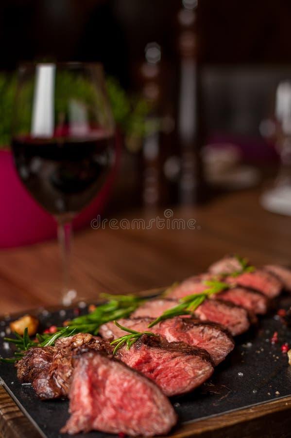 在一张木桌上的切好的红葡萄酒牛排 免版税库存照片