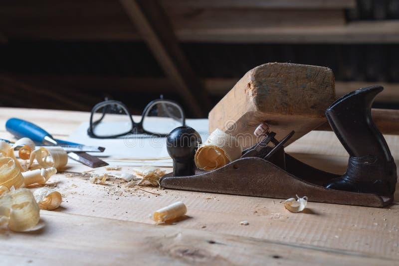 在一张木桌上的工具木匠与锯木屑,整平机,短槌,凿子,风镜 免版税库存照片