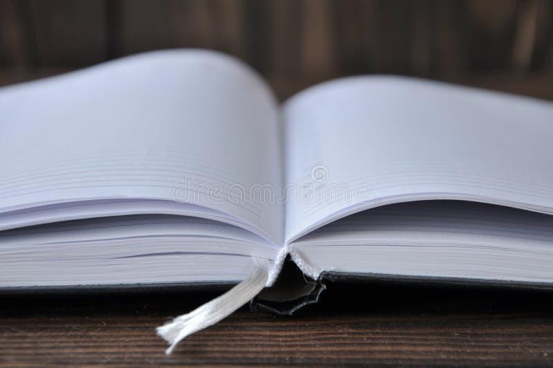 在一张木桌上的开放书或笔记本谎言 免版税库存照片
