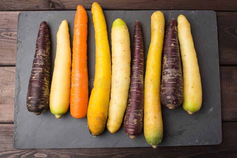 在一张木桌上的新鲜的有机彩虹红萝卜 库存照片