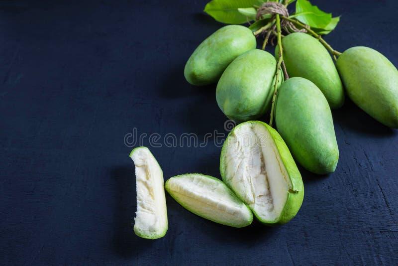 在一张木桌上的新鲜的绿色芒果果子 免版税库存照片