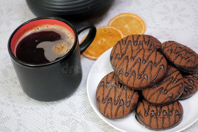 在一张木桌上的涂了巧克力的曲奇饼与一杯咖啡 早餐点心 图库摄影