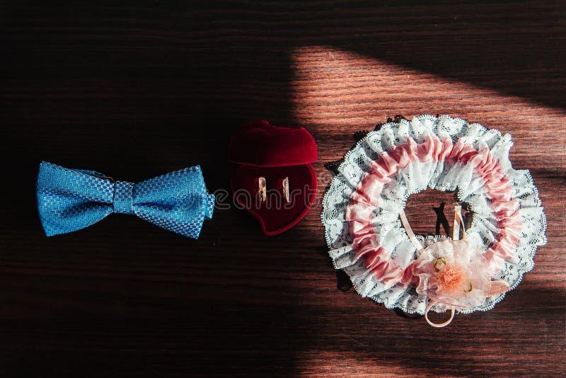 在一张木桌上的结婚戒指、蝴蝶和袜带新娘 免版税图库摄影