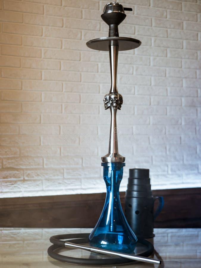 在一张木桌上的美丽的玻璃水烟筒 图库摄影