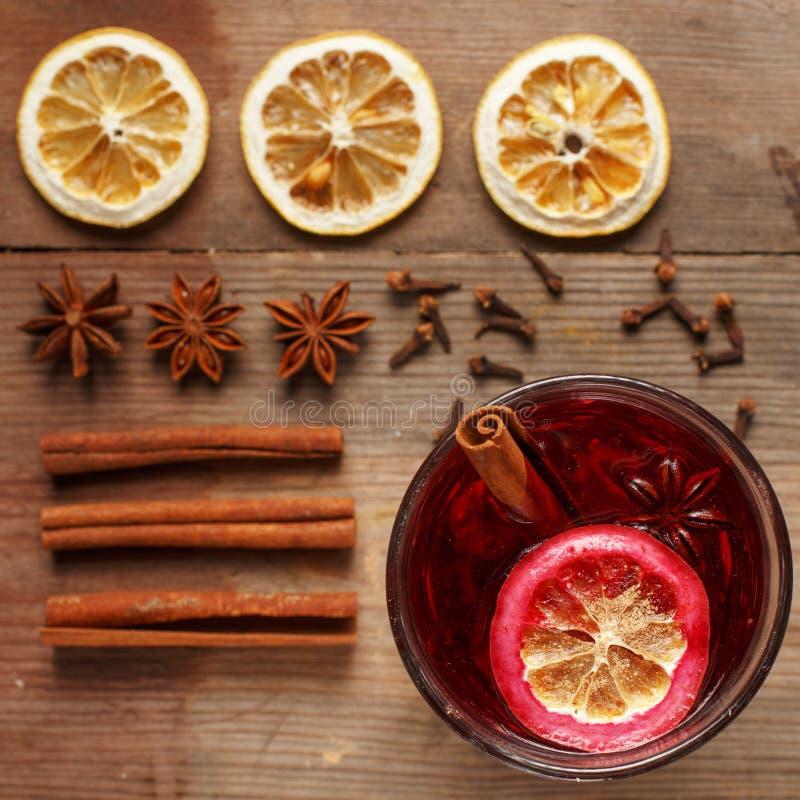 在一张木桌上的芬芳加香料的热葡萄酒 成份 土气 免版税库存照片