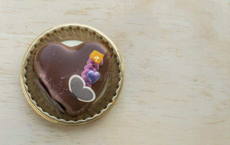 在一张木桌上的花梢心形的巧克力蛋糕 免版税库存照片