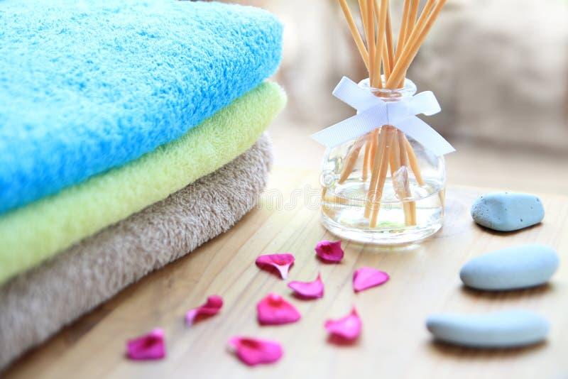 在一张木桌上的芳香疗法芦苇difuser瓶与毛巾、瓣和按摩石头 库存图片