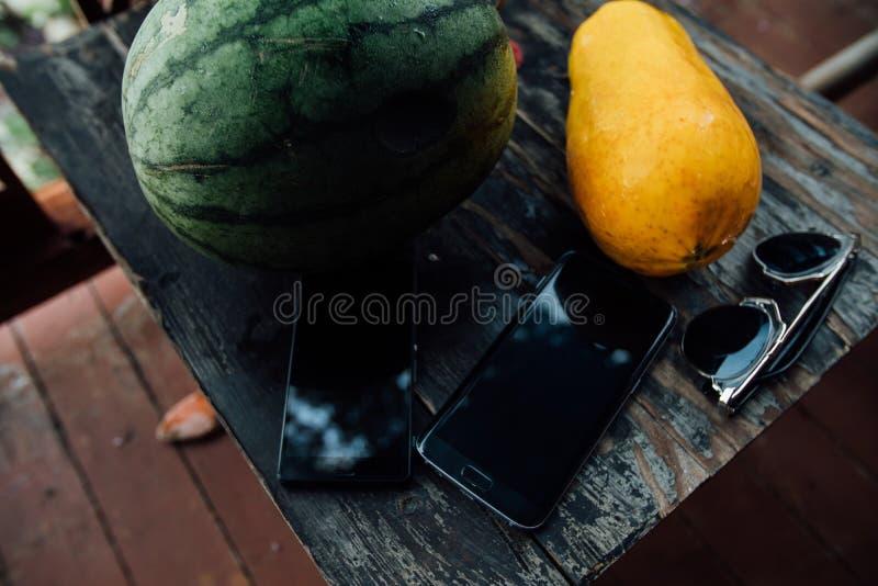 在一张木桌上的西瓜和番木瓜整个谎言在电话和太阳镜旁边 免版税库存图片