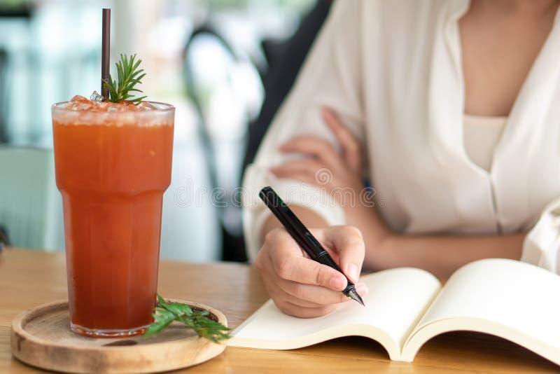 亚洲女孩拿着黑笔在空书里写 日记写作的故事 木桌上的记忆 免版税库存图片