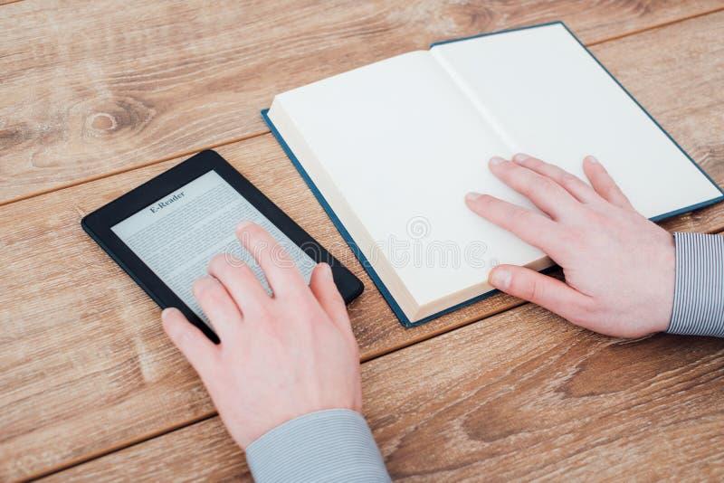 在一张木桌上的E书读者与书 图库摄影