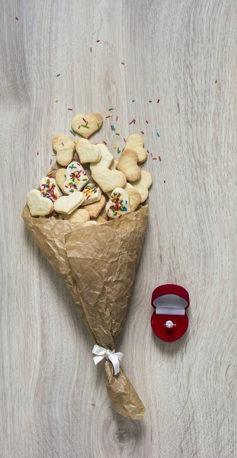 在一张木桌上说谎堆与心脏和一粒多彩多姿的粉末的曲奇饼形式的被弄皱的纸和有钻戒的一个箱子 库存照片