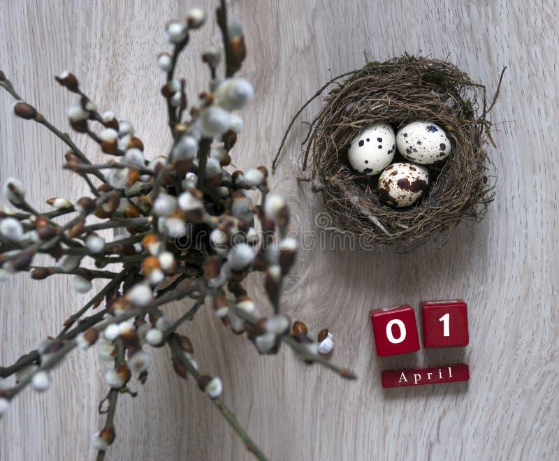 在一张木桌上说谎巢用鸡蛋并且站立有杨柳分支日历复活节立方体的4月一个花瓶 免版税库存图片