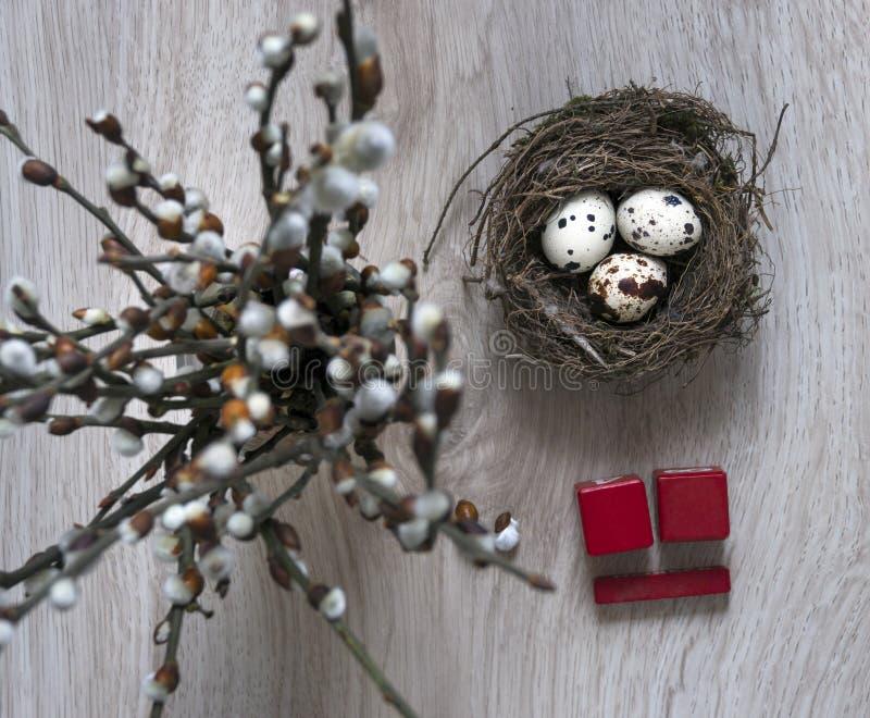 在一张木桌上说谎巢用鸡蛋并且站立有杨柳分支日历复活节立方体的4月一个花瓶 库存图片