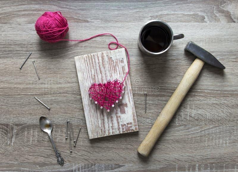 在一张木桌上说谎锤子钉子每杯子螺纹桃红色和您自己的心脏礼物螺纹和钉子的心脏 免版税库存照片