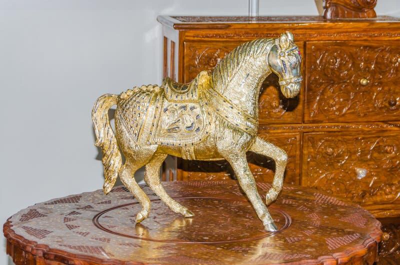 在一张木桌上马的金属雕象 免版税库存照片