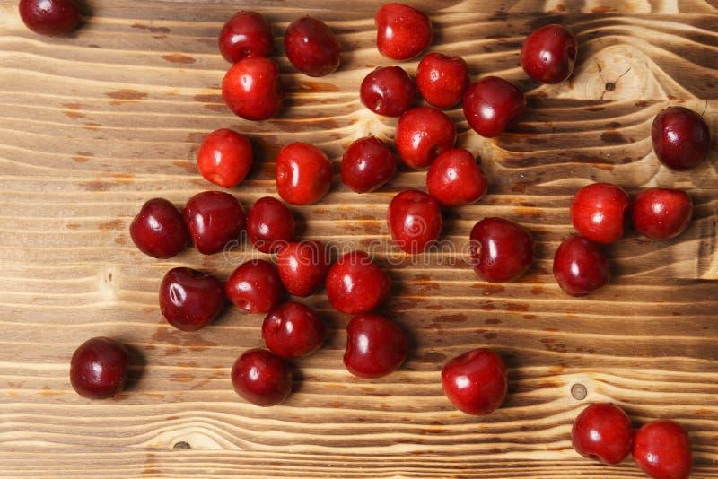 在一张木桌上驱散的红色甜樱桃 免版税库存照片