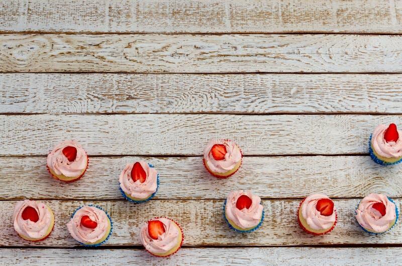 在一张木白色桌上的许多杯形蛋糕从上面 库存图片
