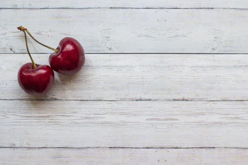 在一张木背景顶视图的樱桃莓果,特写镜头 免版税库存照片