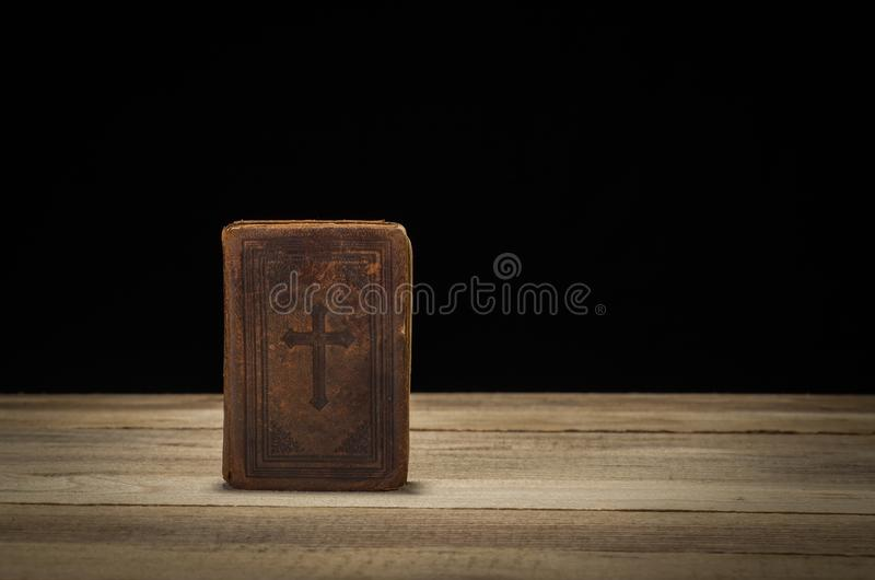 在一张树木繁茂的桌上的圣经 黑色背景 免版税库存图片
