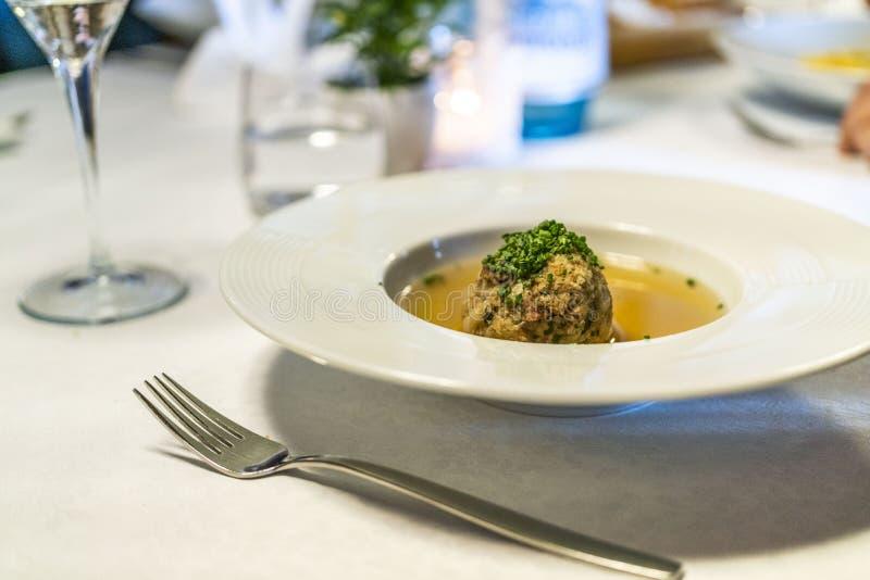 在一张桌上的可口Tyrolian烟肉饺子汤与叉子 库存图片
