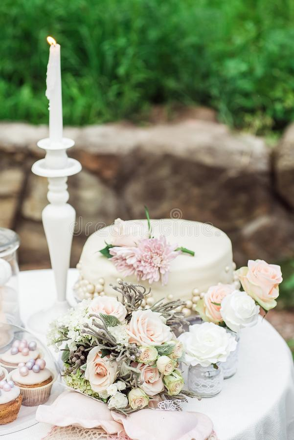 在一张桌上的婚礼花束在蛋糕旁边 免版税库存照片
