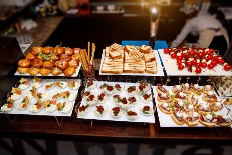 在一张桌上的承办的桌集合服务各种各样的快餐在宴会 设置冷的快餐,点心,饮料,特写镜头 库存图片
