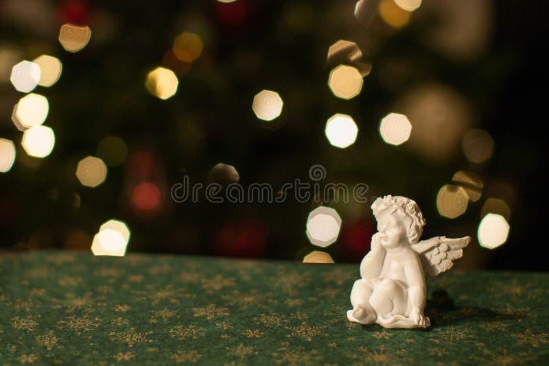在一张桌上的白色天使雕象与与金黄剥落的绿色桌布 免版税库存照片