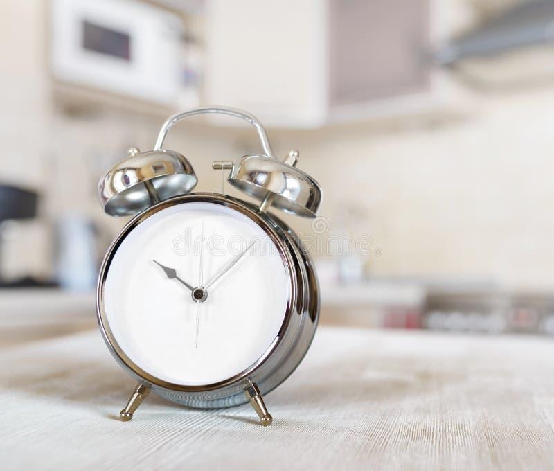 在一张桌上的闹钟在厨房里 图库摄影