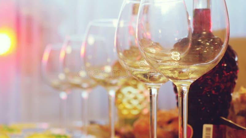 在一张桌上的玻璃玻璃在餐馆,宴会桌,杯酒演出照明设备 免版税图库摄影
