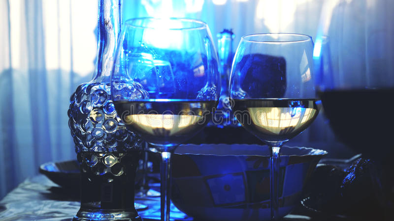 在一张桌上的玻璃玻璃在餐馆,宴会桌,杯酒演出蓝色照明设备 免版税库存照片