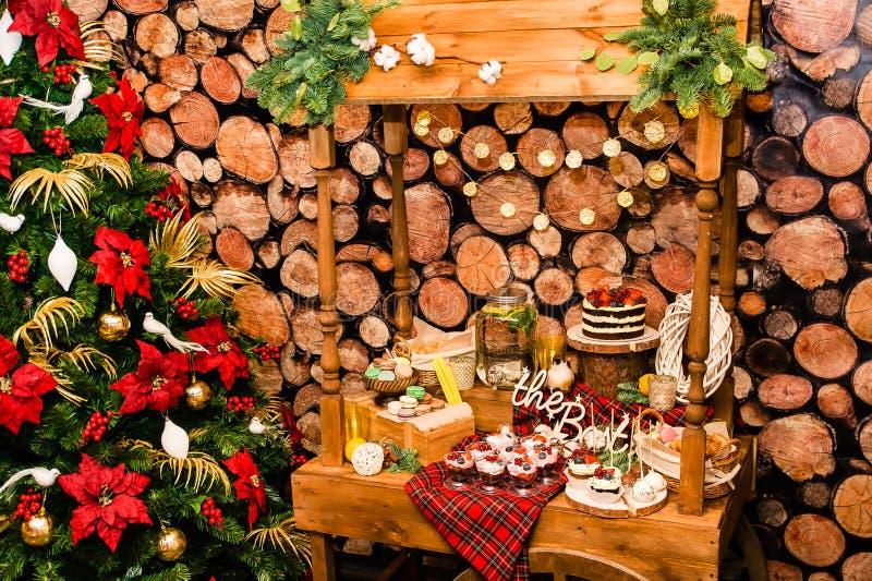 在一张桌附近的圣诞树与在新年装饰的甜点 免版税库存图片