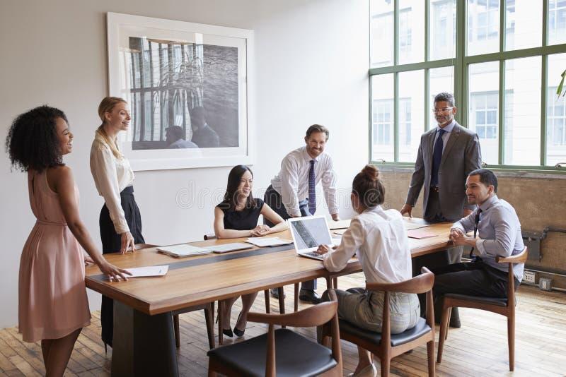 在一张桌附近的年轻专家在业务会议上 免版税库存照片