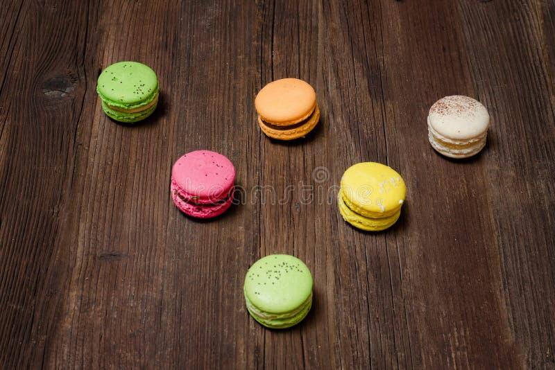 在一张棕色木桌上的六多彩多姿的macarons 顶视图 免版税库存照片