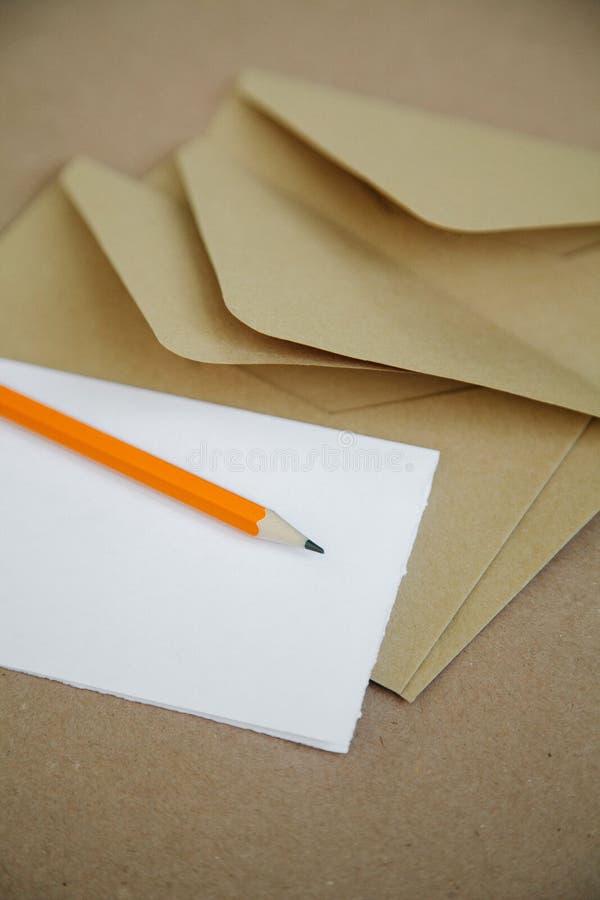 在一张棕色葡萄酒桌上的浪漫笔记和邮件信封 免版税库存图片