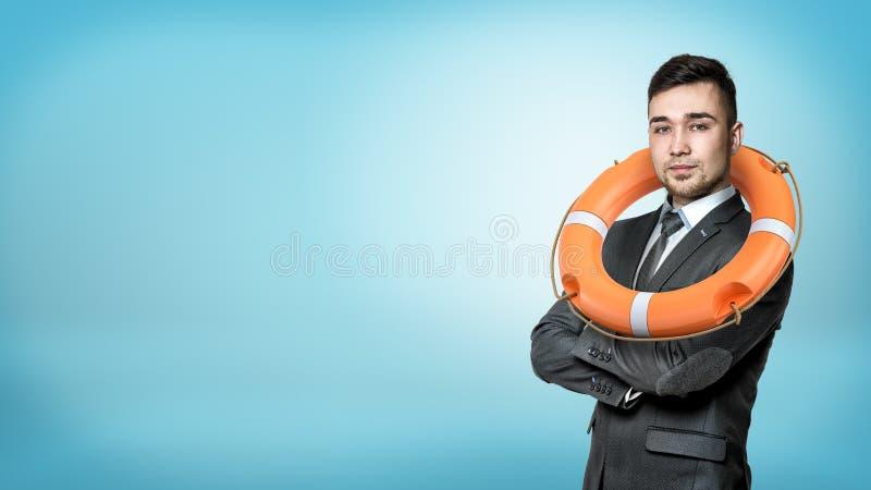 在一张正面图的一个商人用手横渡的和垂悬在他的脖子的橙色救生圈 库存图片