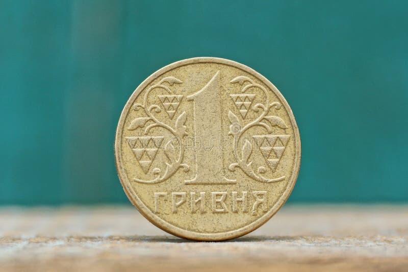 在一张灰色桌上的一枚圆的黄色乌克兰hryvnia硬币在绿色背景 库存图片