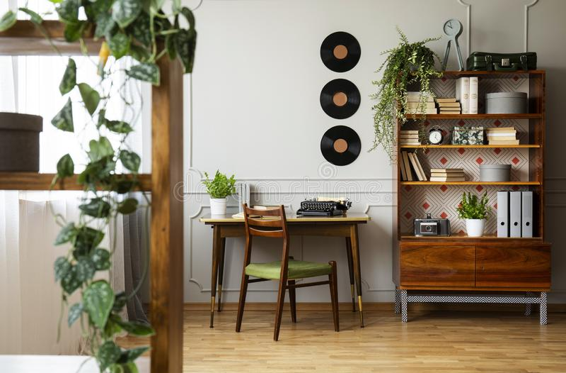 在一张独特的木书桌、中世纪现代椅子和一个被更新的书橱上的黑减速火箭的打字机在相互行家的家庭办公室 免版税库存照片