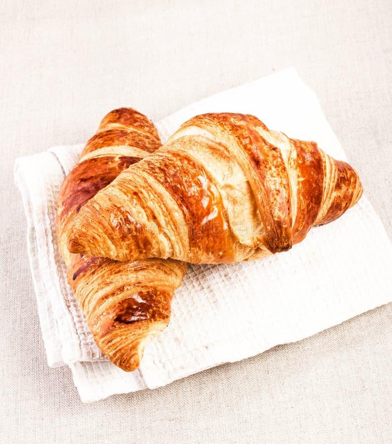 在一张白色亚麻布餐巾的新鲜的新月形面包在米黄桌布ba 免版税库存图片