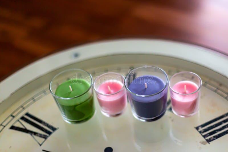 在一张白色手表桌上的四个颜色蜡烛 免版税库存照片