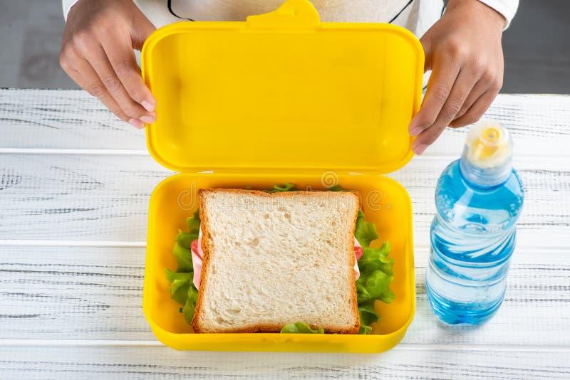 在一张白色木桌上是一饭盒用多士用火腿和莴苣和塑料瓶水 E 免版税库存照片